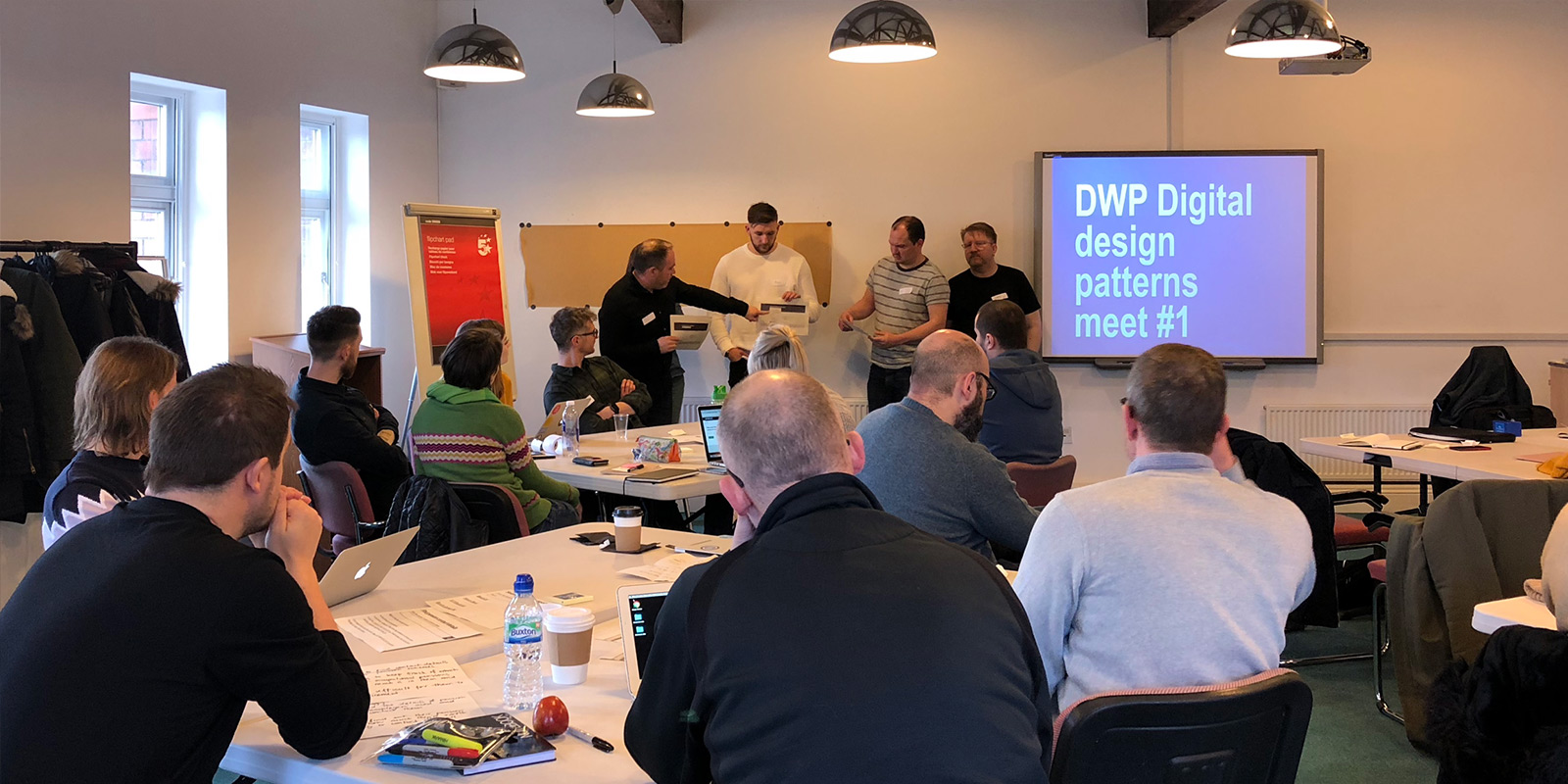 DWP Digital designers in a room listening to colleagues presenting their work